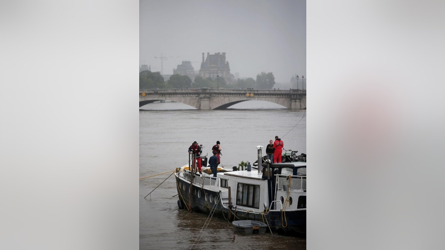 Firemen inspect a barge on the Seine river during floods, in Paris, Sunday, June 5, 2016. The riverside Grand Palais exhibition hall in Paris reopened Sunday as floodwaters slowly receded from the French capital, though risks remain for other regions. (AP Photo/Thibault Camus)