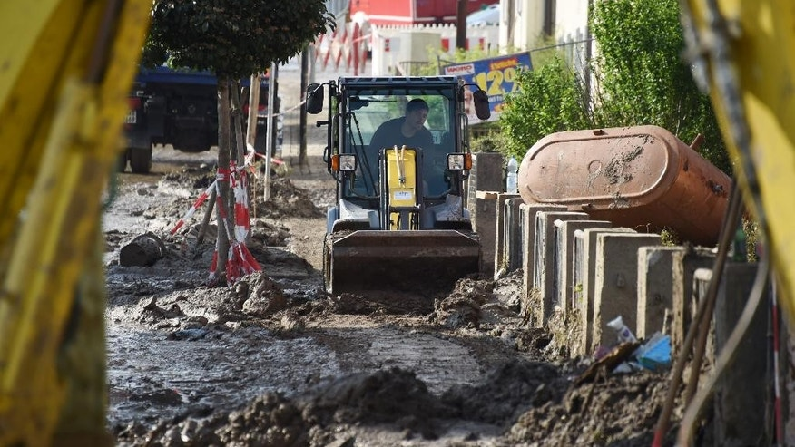 A man in an excavator clears  mud from a street in Simbach, southern Germany, Monday, June 6, 2016. Germany, has been hit by severe storms that have caused heavy flooding in recent days. (Tobias Hase/dpa via AP)