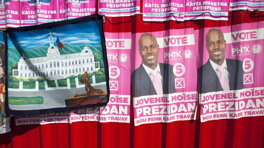 FILE - In this Oct. 10, 2015 file photo, campaign posters promoting presidential candidate Jovenel Moise, of the PHTK political party, cover metal sheeting behind a painting for sale of the National Palace in Port-au-Prince, Haiti. The electoral council of Haiti has decided to re-do a presidential election that a special commission determined was marred by fraud. Provisional Electoral Council President Leopold Berlanger said Monday, June 6, 2016, a first round vote will be held Oct. 9. If no one secures a majority, it will be followed by a runoff for the top two contenders on Jan. 8. (AP Photo/Dieu Nalio Chery, File)