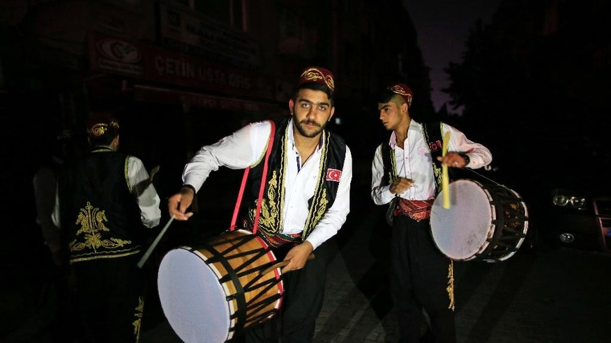 "On the first day of the Muslim holy month of Ramadan, drummers, wearing traditional Ottoman clothes, perform through the neighborhoods of Istanbul, early Monday June 6, 2016 to wake people for the ""sahour"", the traditional breakfast of Ramadan. More than 2000 drummers wander Istanbul's neighborhoods playing their drums in the early hours to wake up the residents as part of the holiday tradition. (AP Photo/Lefteris Pitarakis)"