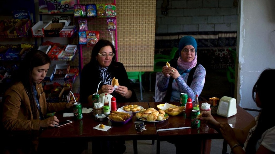 In this Friday, May 27, 2016 photo, Brazilian-Lebanese women have a Brazilian breakfast at the Pastelaria de Tina Restaurant in the village of Sultan Yaacoub, 9 kilometers (5 miles) from the Syrian border with Lebanon. At the eastern edge of the rural Bekaa Valley, where the rocky hillsides are stippled with cherry trees, a generations-old kinship with Brazil has imbued two Lebanese villages with a Latino spirit. Lusi and Sultan Yaacoub are home to more than one thousand Brazilian nationals, many of whom speak Portuguese as fluently as they do Arabic. (AP Photo/Hassan Ammar)