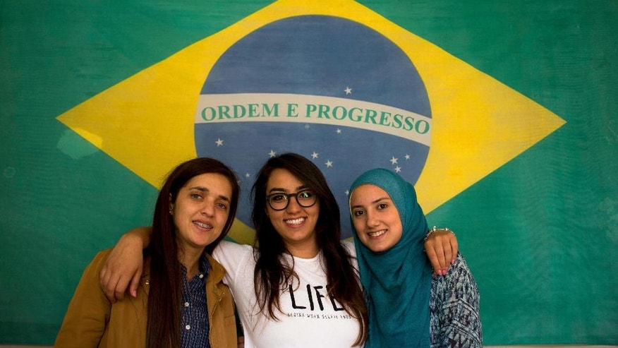 In this Friday, May 27, 2016 phoot, Brazilian-Lebanese women from left to right, Fatima Wehbi, Lilwah Smidi and Maysoun Hindi pose for a picture with a Brazilian flag in the village of Sultan Yaacoub, 9 kilometers (5 miles) from the Syrian border with Lebanon. At the eastern edge of the rural Bekaa Valley, where the rocky hillsides are stippled with cherry trees, a generations-old kinship with Brazil has imbued two Lebanese villages with a Latino spirit. Lusi and Sultan Yaacoub are home to more than one thousand Brazilian nationals, many of whom speak Portuguese as fluently as they do Arabic. (AP Photo/Hassan Ammar)