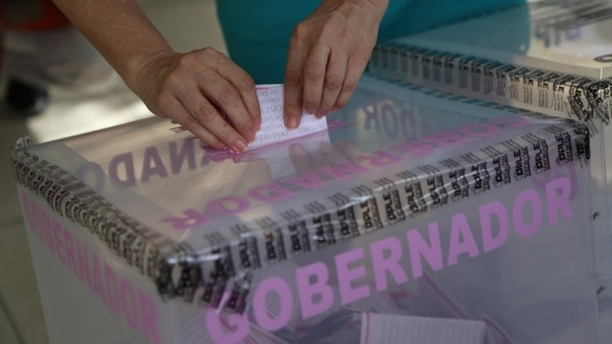 A woman casts her vote during state elections in the city of Veracruz, Mexico, Sunday, June 5, 2016. Veracruz is the biggest prize in Sunday's gubernatorial elections, which could shape the fortunes of the country's ruling Institutional Revolutionary Party in its bid to hold onto the presidency in 2018. In five of the 12 statehouses up for grabs, including Veracruz, the party has ruled uninterrupted for more than 80 years. (AP Photo/Ilse Huesca)