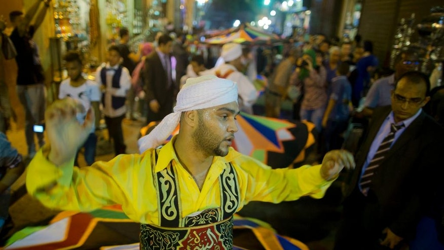 In this Sunday, June 5, 2016 photo, whirling dervishes spin during a performance to mark the holy month of Ramadan at El-Moez Street in historical Fatimid Cairo, Egypt. Devout Muslims began to celebrate Ramadan, the holiest month in the Islamic calendar, refraining from eating, drinking, smoking and sex from sunrise to sunset. (AP Photo/Amr Nabil)