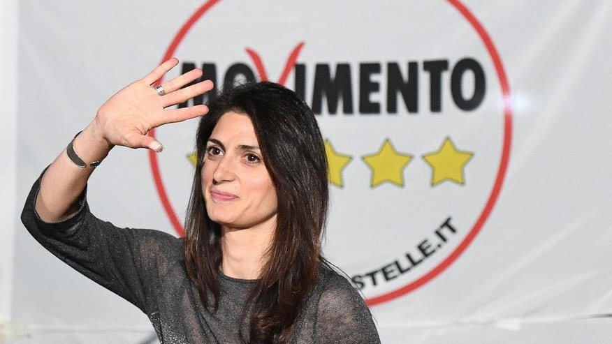 Virginia Raggi, of the 5-Star Movement, waves to supporters in Rome, Monday, June 6, 2016. Raggi, an anti-establishment candidate in Rome, has comfortably clinched a runoff mayoral election slot, as Romans disgusted by corruption scandals and deteriorating city services largely turned away from traditional left and right parties which governed the Italian capital for decades. (Alessadnro Di Meo/ANSA Via AP)