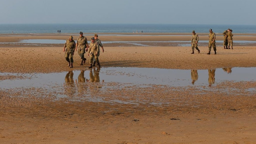 CORRECTS YEAR TO 2016- WWII enthusiasts from Spain wearing 101st Airbone gears walk on Omaha beach next to the Colleville American military cemetery, in Colleville sur Mer, western France, Sunday June 5, 2016, on the eve of the 72nd anniversary of the D-Day landing. D-Day marked the start of a Europe invasion, as many thousands of Allied troops began landing on the beaches of Normandy in northern France in 1944 at the start of a major offensive against the Nazi German forces, an offensive which cost the lives of many thousands. (AP Photo/Francois Mori)