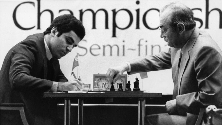 FILE - In this Nov. 25, 1983 file photo, Garry Kasparov, 20, left, the young Soviet number 2, makes notes as his opponent Russian exile Victor Korchnoi makes a move during the World Chess Championship semi-final in London. Chess grandmaster Victor Korchnoi, a prominent Soviet defector who saw his citizenship restored by Mikhail Gorbachev in the waning days of the USSR, has died on Monday, June 6, 2016. He was 85. The Russian chess federation says Korchnoi died in Switzerland, where he had lived for decades. (AP Photo/Taggart, file)