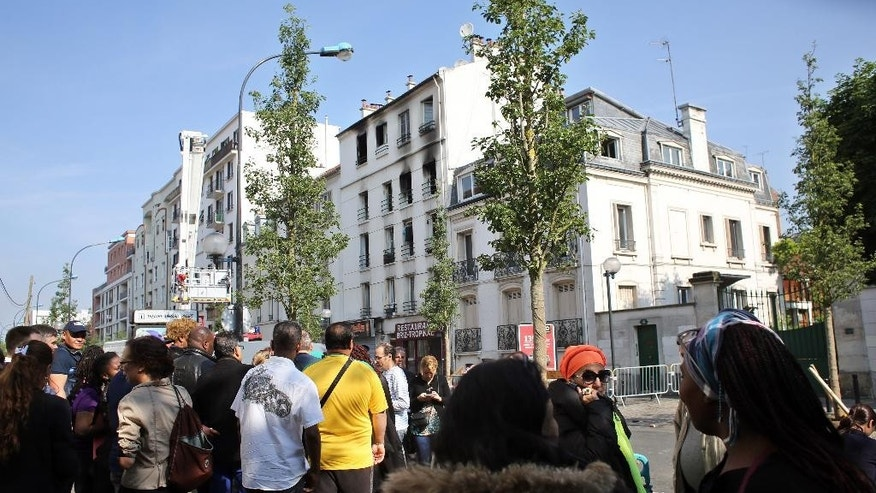 People gather next to a burned building, in Saint-Denis, north of Paris, Tuesday, June 7, 2016. A fire in an apartment building near France's national stadium left at least five people dead and 11 injured. (AP Photo/Thibault Camus)