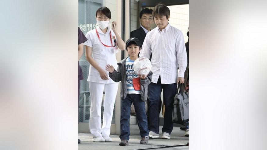 Yamato Tanooka, center, who was found after being abandoned by his parents as punishment in a forest, is escorted by his father Takayuki, right, as he leaves a hospital in Hakodate on the northern island of Hokkaido Tuesday, June 7, 2016. The seven-year-old boy was discharged Tuesday afternoon. (Daisuke Suzuki/Kyodo News via AP)  JAPAN OUT, MANDATORY CREDIT