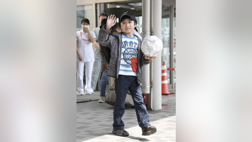 Yamato Tanooka, who was found after being abandoned by his parents as punishment in a forest, waves as he leaves a hospital in Hakodate on the northern island of Hokkaido Tuesday, June 7, 2016. The seven-year-old boy was discharged Tuesday afternoon. (Daisuke Suzuki/Kyodo News via AP)  JAPAN OUT, MANDATORY CREDIT