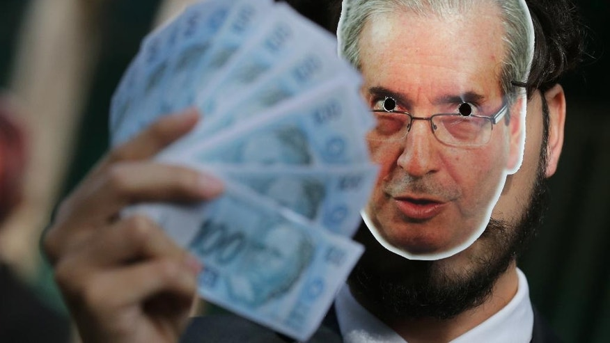A demonstrator from the Avaaz organization wears a mask photograph of the former Lower House Speaker Eduardo Cunha, as he holds up fake money outside Congress in Brasilia, Brazil, Tuesday, June 7, 2016. Cunha is facing allegations of lying to congress by denying holding overseas bank accounts, and has been charged with corruption and obstruction of justice. (AP Photo/Eraldo Peres)