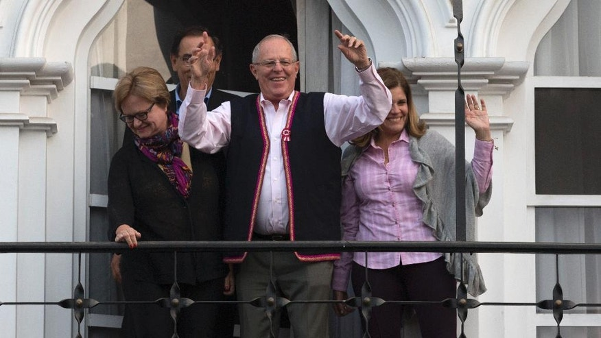 Flanked by his running mates Mercedes Araoz, right, and Martin Vizcarra, presidential candidate Pedro Pablo Kuczynski acknowledges supporters and reporters gathered outside his home in Lima, Peru, Monday, June 6, 2016. Kuczynski had a razor-thin lead over his rival Keiko Fujimori, the daughter of jailed former strongman Alberto Fujimori, as Peruvians awaited results still trickling in from remote parts of the Andean nation.  Kuczynski's wife Nancy Lange is pictured at left. (AP Photo/Silvia Izquierdo)
