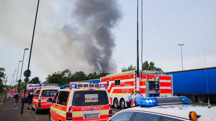 Rescue cars stand near a refugee accommodation on the grounds of the convention center where a fire has broken in the western city of Duesseldorf, Tuesday, June 7, 2016. Joerg Schmitter, spokesman of the local fire department told The Associated Press that the fire started shortly after noon on Tuesday. He said that all people who had been in the hall appeared to have made it out. (Rolf Vennenbernd/dpa via AP)
