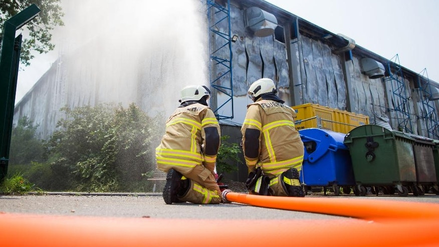 Firefighters try to extinguish a fire that has broken at a refugee accommodation on the grounds of the convention center in the western city of Duesseldorf, Tuesday, June 7, 2016. Joerg Schmitter, spokesman of the local firedepartment told The Associated Press that the fire started shortly after noon on Tuesday. He said that all people who had been in the hall appeared to have made it out. (Rolf Vennenbernd/dpa via AP)