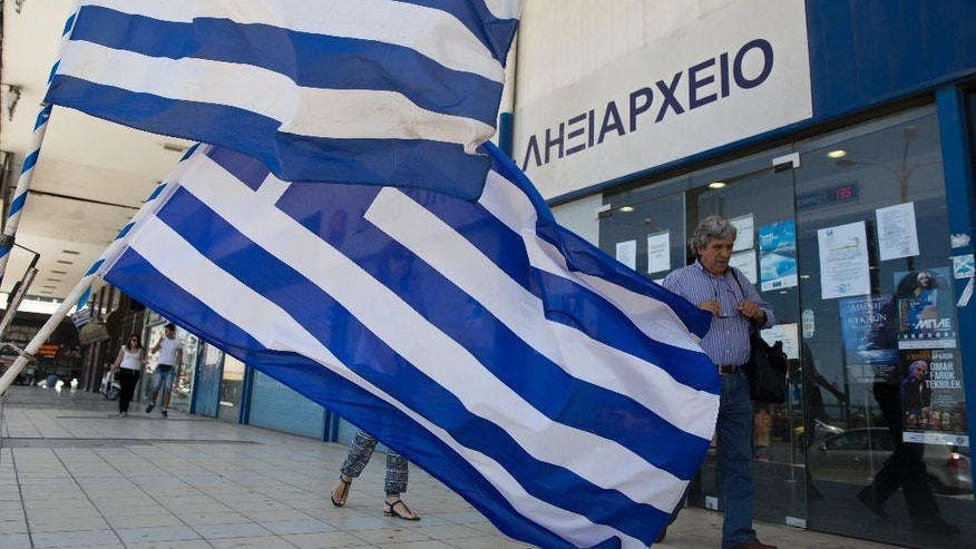 Pedestrians walk in front of a civil registry office as Greek flags are displayed for sale in the foreground at Athens' main port of Piraeus on Monday, June 6, 2016. Bailout lenders on Monday were reviewing new Greek austerity measures demanded to release the next installments of rescue loans for Athens. (AP Photo/Petros Giannakouris)