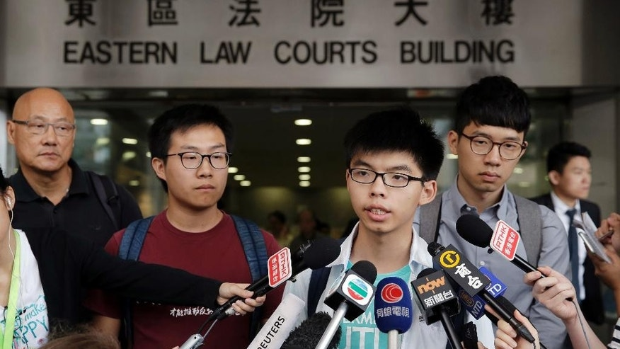 Pro-democracy leader Joshua Wong, second right, speaks to media outside a district court in Hong Kong, Tuesday, June 7, 2016. A Hong Kong court has acquitted teen pro-democracy leader Joshua Wong of obstructing police at a protest two years ago against China's tightening hold on the city. A magistrate on Tuesday found Wong and three others not guilty, according to a post on the Facebook page of his political party, Demosisto. (AP Photo/Kin Cheung)