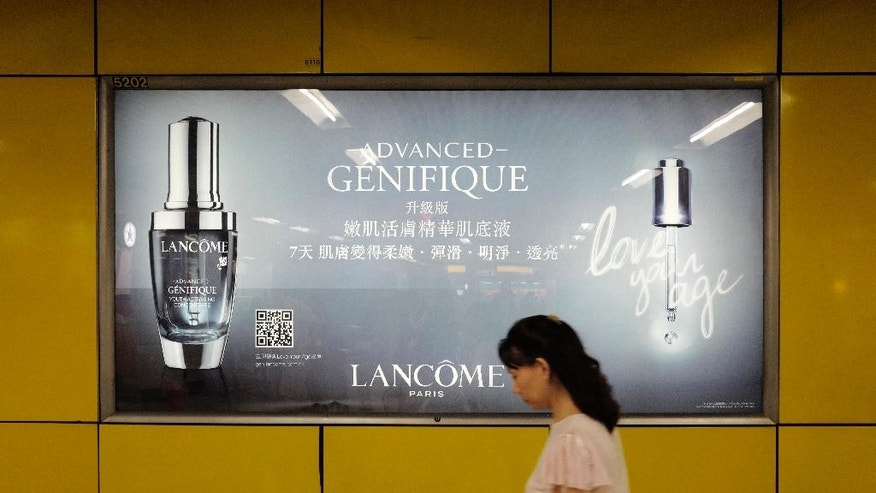 A woman walks past an advertising light box showing products of French cosmetics company Lancome at a subway station in Hong Kong Tuesday, June 7, 2016. French cosmetics company Lancome has sparked a backlash in Hong Kong after it canceled a promotional concert featuring a singer known for pro-democracy views, with many accusing it of caving to political pressure from Beijing. (AP Photo/Vincent Yu)