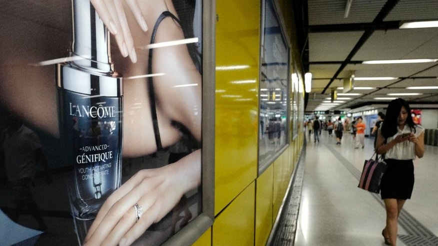 A woman walks past an advertising light box showing a product of French cosmetics company Lancome at a subway station in Hong Kong Tuesday, June 7, 2016. French cosmetics company Lancome has sparked a backlash in Hong Kong after it canceled a promotional concert featuring a singer known for pro-democracy views, with many accusing it of caving to political pressure from Beijing. (AP Photo/Vincent Yu)