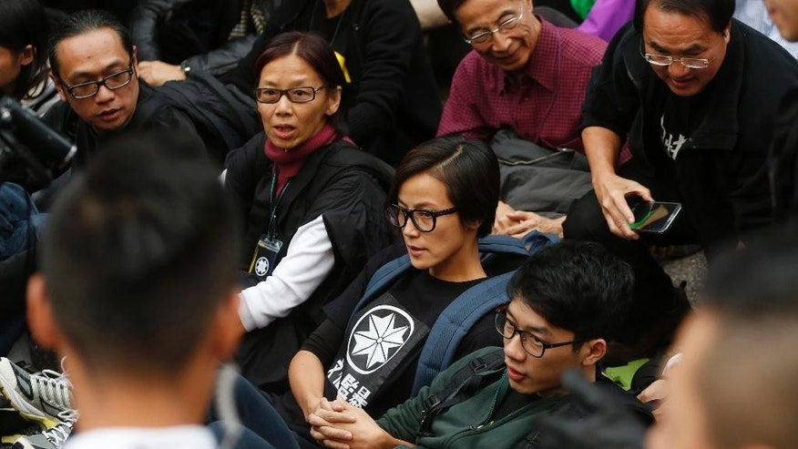 "FILE - In this Dec. 11, 2014, file photo, Cantopop singer and outspoken celebrity activist Denise Ho, center, accompanied with other protesters attends a sit-in rally at the occupied area outside government headquarters in Hong Kong. French cosmetics company Lancome has sparked a backlash in Hong Kong after it canceled a promotional concert featuring the singer known for pro-democracy views, with many accusing it of caving to political pressure from Beijing. Lancome said Sunday, June 5, 2016 on its Hong Kong Facebook page that the event had been canceled because of unspecified ""safety reasons."" It It also sought to distance itself from Ho in a separate post, saying that she's not its spokesperson. (AP Photo/Kin Cheung, File)"