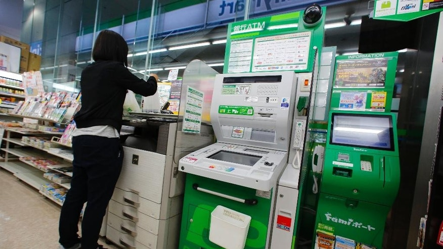 A woman uses a copy machine placed next to an ATM at a convenience store in Tokyo, Tuesday, June 7, 2016. Japanese banks that lost some 1.8 billion yen ($16.5 million) when fake overseas cards were used at convenience store ATMs are scrambling to combat such fraud. The illegal withdrawals were made in just a few hours on May 15 at more than 1,000 ATMs in 17 prefectures (states), according to Japanese media reports. (AP Photo/Shizuo Kambayashi)