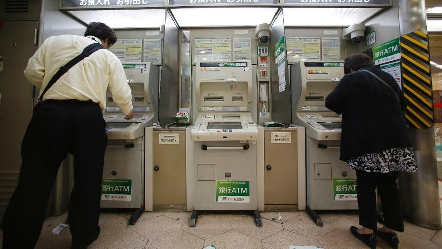 People use ATMs at a railway station in Tokyo, Tuesday, June 7, 2016. Japanese banks that lost some 1.8 billion yen ($16.5 million) when fake overseas cards were used at convenience store ATMs are scrambling to combat such fraud. The illegal withdrawals were made in just a few hours on May 15 at more than 1,000 ATMs in 17 prefectures (states), according to Japanese media reports. (AP Photo/Shizuo Kambayashi)