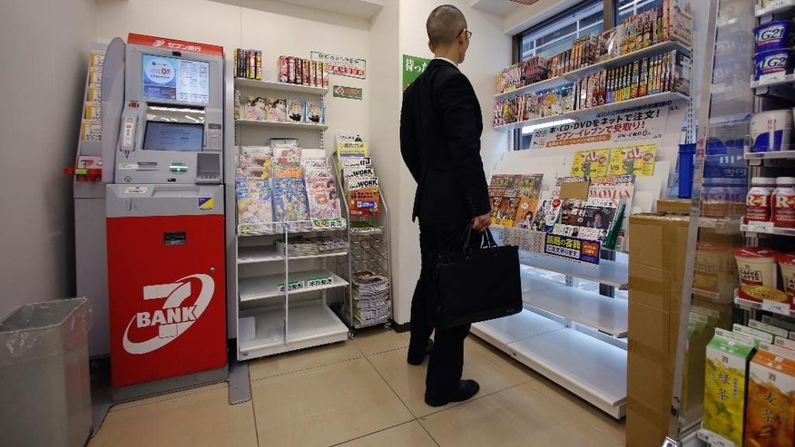 A man looks at magazines near an ATM at a convenience store in Tokyo, Tuesday, June 7, 2016. Japanese banks that lost some 1.8 billion yen ($16.5 million) when fake overseas cards were used at convenience store ATMs are scrambling to combat such fraud. The illegal withdrawals were made in just a few hours on May 15 at more than 1,000 ATMs in 17 prefectures (states), according to Japanese media reports. (AP Photo/Shizuo Kambayashi)