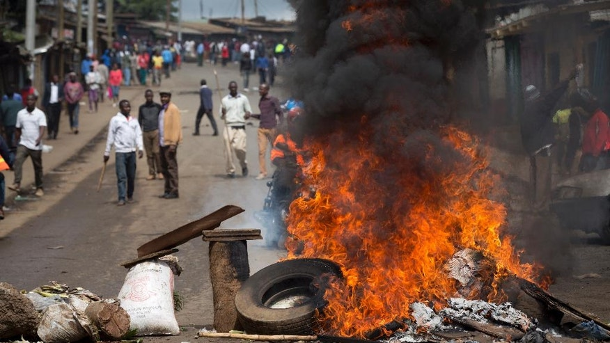 Protesters carrying sticks and rocks stand behind a barricade of burning tyres, as they call for the disbandment of the national electoral commission over allegations of bias and corruption, in the Kibera slum of Nairobi, Kenya Monday, June 6, 2016. While demonstrations led by opposition leaders in the capital were largely peaceful, police in the western town of Kisumu tear-gassed demonstrators who responded by throwing stones and witnesses say some people were killed by police. (AP Photo/Ben Curtis)