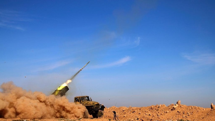 FILE - In this file photo taken on Wednesday, Feb. 17, 2016, soldiers from the Syrian army fire a rocket at Islamic State group positions in the province of Raqqa, Syria. A two-pronged advance to capture key urban strongholds of the Islamic State, and the extremist group's self-styled capital of Raqqa has underlined a convergence of strategy between Washington and Moscow to defeat the extremist group, with Syria's Kurds emerging as the common denominator. (Alexander Kots/Komsomolskaya Pravda via AP, File)