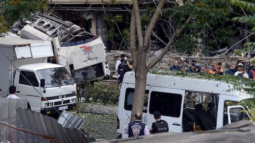 Turkish police officers work at the scene of a blast just after an explosion in Istanbul, Tuesday, June 7, 2016. A car bomb attack targeting a bus carrying riot police during rush hour traffic in Istanbul on Tuesday has killed number of people and wounded dozens others, the city's governor said.(IHA via AP) TURKEY OUT