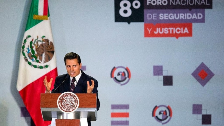 Mexican President Enrique Pena Nieto speaks to the 8th National Forum for Security and Justice, in Mexico City, Tuesday, June 7, 2016. On the same day that Pena Nieto spoke at the forum, the international program Open Society Justice Initiative released a report saying the Mexican government has committed crimes against humanity in its war against drug cartels. (AP Photo/Rebecca Blackwell)