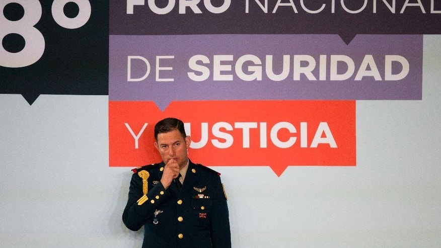 A presidential guard stands in front of the logo for the 8th National Forum for Security and Justice, in Mexico City, Tuesday, June 7, 2016. Mexican President Enrique Pena Nieto spoke at the forum Tuesday, on the same day the international program Open Society Justice Initiative released a report saying the Mexican government has committed crimes against humanity in its war against drug cartels. (AP Photo/Rebecca Blackwell)