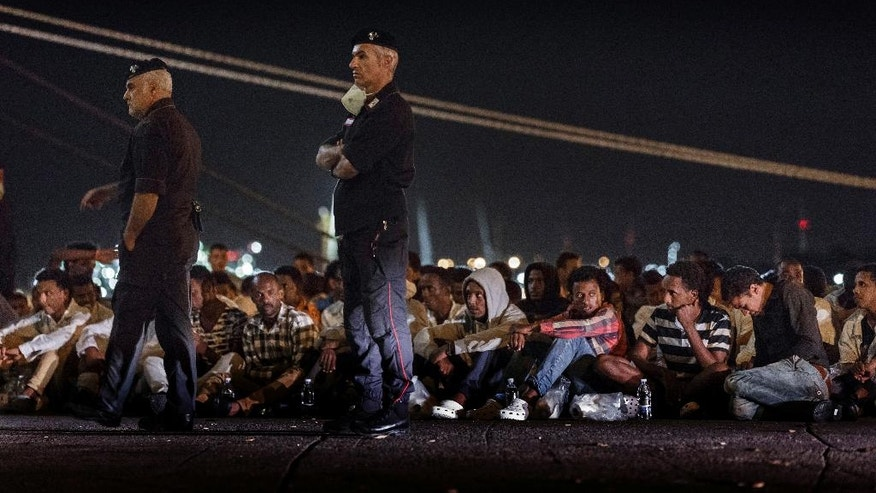 Migrants sit on the dock after disembarking from the Clipper Hebe, the ship that rescued them, upon arrival at the port of Augusta, on the island of Sicily, Italy, Saturday, June 4, 2016. The Norwegian tanker carrying 221 migrants who survived a shipwreck Friday arrived at the Italian port on the island of Sicily with the body of a migrant who drowned in Friday's shipwreck of a smuggling boat that sank in the southern Mediterranean Sea. The human trafficking route from North Africa to southern Europe has claimed the lives of over 1,000 migrants in the last two weeks. (AP Photo/Daniel Ochoa de Olza)