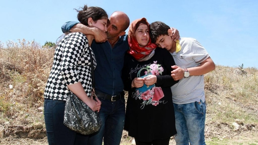 FILE - In this Monday, May 30, 2016 file photo, Rashid Jaqali, second from left, hugs his daughter Yehia, left, his wife Fatima, second from right, and his son Suranne as they mourn their family member Mohammed who died in the May 25 shipwreck in Siculiana, Italy. The Jaqali family was crammed into the metal fishing boat, packed with more than 700 migrants on their way from Libya to Italy. Father, mother and daughter squeezed together at the front of the bow, while the two sons were split up on either side. When help finally came, they all got off the boat except for the oldest son, Mohammed. He couldn't move and waved to the others, motioning: I will follow you. The Jaqalis are among more than 20,000 people who have made the perilous sea journey from North Africa to Europe in overcrowded boats so far this year.  (AP Photo/Pasquale Claudio Montana Lampo, File)