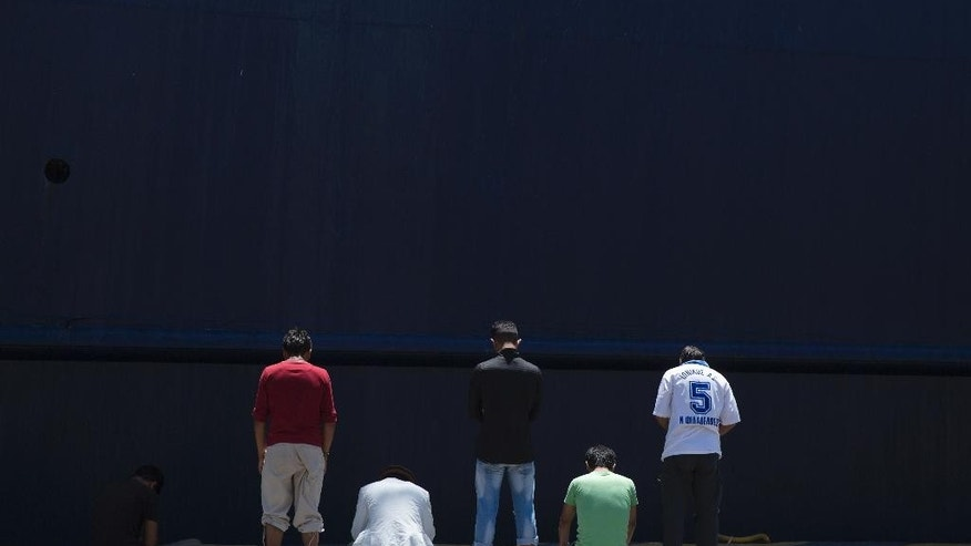 Afghan migrants stranded in Greece, pray in front of a docked ferry at the port of Piraeus , near Athens on the first day of the holy fasting month of Ramadan on Monday, June 6, 2016. During Ramadan, the holiest month in Islamic calendar, Muslims refrain from eating, drinking, smoking and sex from dawn to dusk. (AP Photo/Petros Giannakouris)
