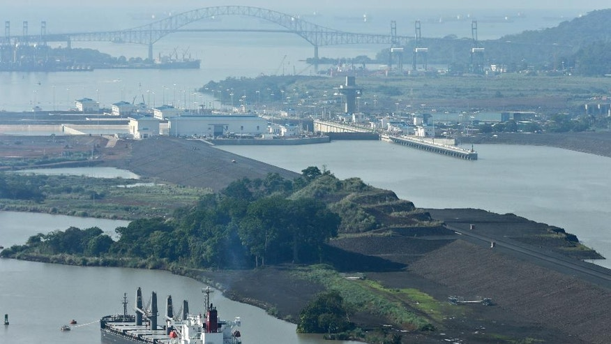 In this May 26, 2016 photo, tugboats guide a cargo ship to the Panama Canal's Miraflores locks near Panama City. A formal inauguration of the $5.25 billion canal expansion is planned for June 26. The project was originally supposed to be completed in October 2014. (AP Photo/Arnulfo Franco)