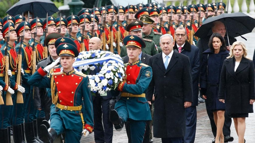 Israeli Prime Minister Benjamin Netanyahu, center, and his wife Sara, right, attend a wreath laying ceremony at the Tomb of Unknown Soldier near the Kremlin Wall in Moscow, Tuesday, June 7, 2016. Netanyahu is Russia on an official two-day visit. (Maxim Shipenkov/Pool photo via AP)
