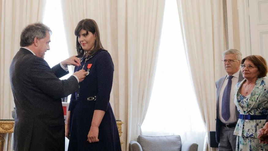 Romania's chief anti-corruption prosecutor Laura Codruta Kovesi, right, receives the French Legion of honor from French Ambassador Francois Saint-Paul as her parents Ileana and Ioan Lascu, right, watch, during a ceremony in Bucharest, Romania, Tuesday, June 7, 2016. Kovesi, who has been praised by EU countries and the U.S. for her anti-corruption fight received one of France's highest honors, the Legion of Honor in recognition of her work . (AP Photo/Vadim Ghirda)