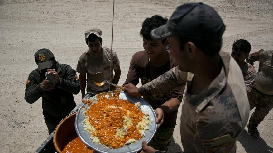 Iraqi counterterrorism forces take their lunch on their front line position during an operation to oust Islamic State militants from Fallujah, Iraq, Tuesday, June 7, 2016. It's the first fasting day of the Muslim holy month of Ramadan - the country's most influential Shiite cleric said Monday that Iraqi fighters could obtain from the Ramadan fast if they thought it impaired their ability on the battlefield. (AP Photo/Maya Alleruzzo)