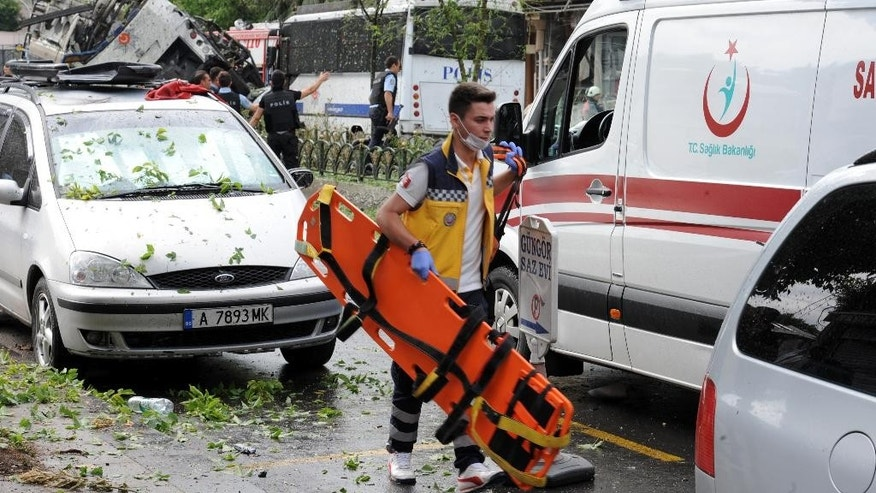 A Turkish medic rushes in to work at the explosion site after a bus carrying riot police official was struck by a bomb in Istanbul, Tuesday, June 7, 2016. At least five police officers were wounded. The blast occurred at a busy intersection near an Istanbul University building in the city's Beyazit district during the morning rush hour. (DHA via AP) TURKEY OUT