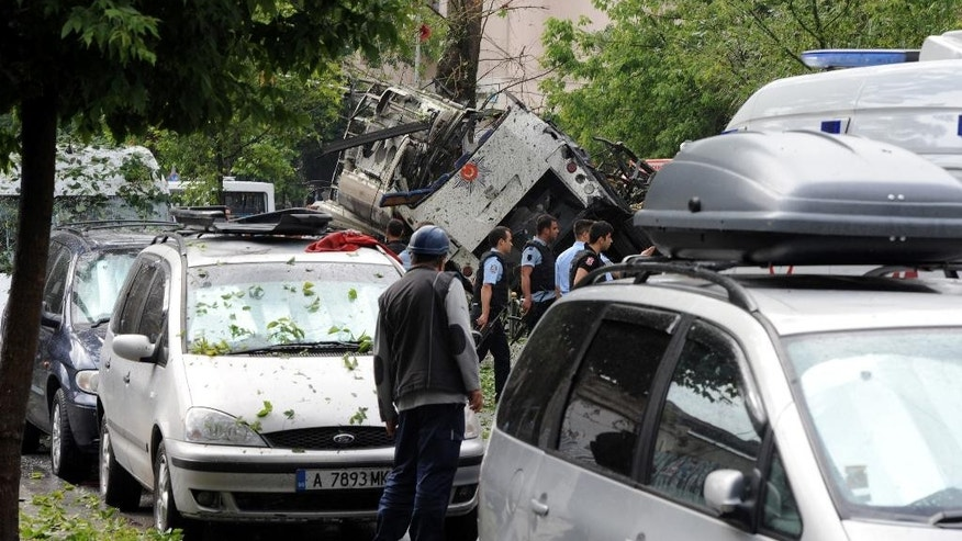 Turkish security officials and firefighters work at the explosion site after a bus carrying riot police official was struck by a bomb in Istanbul, Tuesday, June 7, 2016. At least five police officers were wounded. The blast occurred at a busy intersection near an Istanbul University building in the city's Beyazit district during the morning rush hour. (DHA via AP) TURKEY OUT