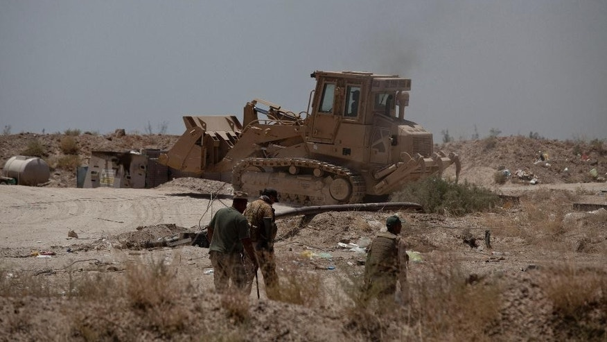 An Iraqi counterterrorism forces soldier drives a mine-resistant bulldozer as Iraqi Army sliders walk together on their front line position during an operation to oust Islamic State militants from Fallujah, Iraq, Tuesday, June 7, 2016. (AP Photo/Maya Alleruzzo)