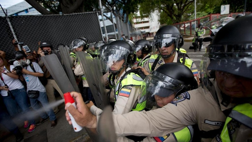 A Bolivarian National Police officer aims pepper spray at opposition leader Henrique Capriles during a protest in Caracas, Venezuela, Tuesday, June 7, 2016. Capriles was repulsed by police who threw tear gas when opposition leader and hundreds of demonstrators were trying to enter the main Caracas Highway to march towards the headquarters of the National Electoral Council or CNE to demand the government allow it to pursue a recall referendum against President Nicolas Maduro. (AP Photo/Fernando Llano)