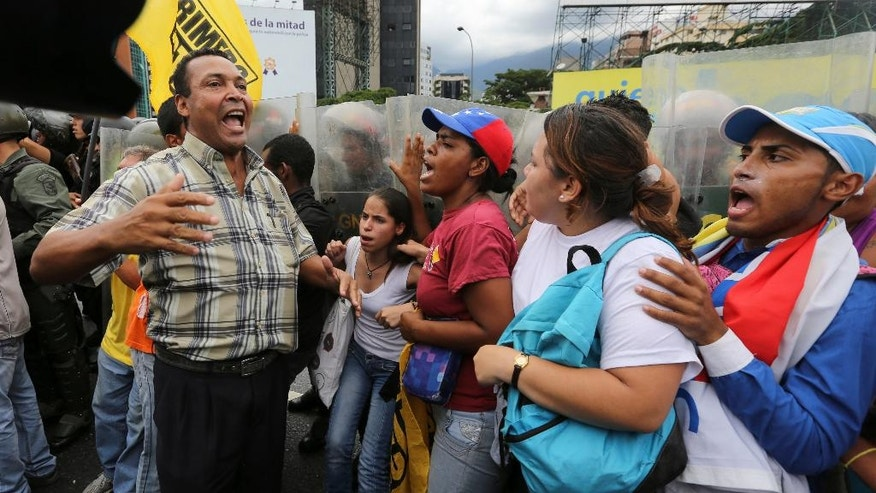 Opposition protesters shout slogans against Venezuela's President Nicolas Maduro in front of a line of police blocking them on Francisco Fajardo highway in Caracas, Venezuela, Tuesday, June 7, 2016. Protesters were turned back from the headquarters of Venezuela's electoral body where the group attempted to march to demand the government allow it to pursue a recall referendum against Maduro. (AP Photo/Fernando Llano)