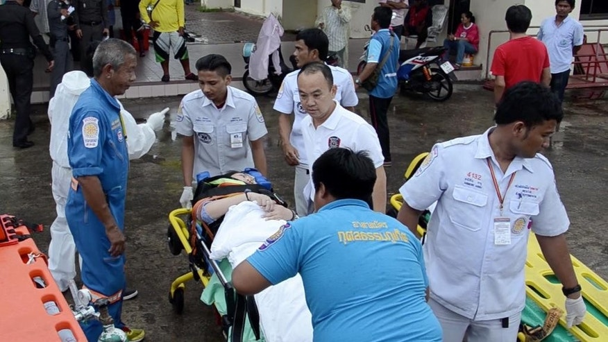 A passenger taken by stretcher from a police rescue boat at a pier in Phuket.