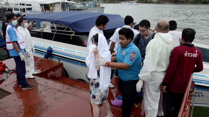 A passenger assisted from a police rescue boat at a pier in Phuket.