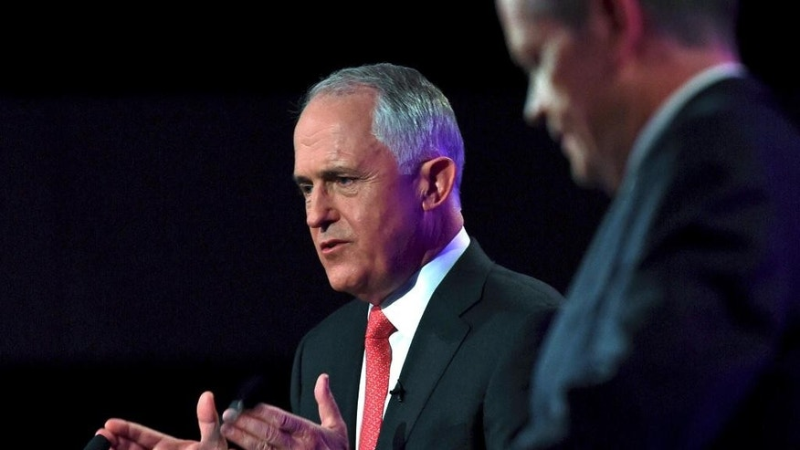In this May 29, 2016, file photo, Australian Prime Minister Malcolm Turnbull, left, speaks as opposition leader Bill Shorten listens at a leaders' debate at the National Press Club in Canberra. Opinion polls suggest the conservative coalition government remains neck-and-neck with the center-left Labor Party opposition since the July 2, 2016 election was officially called early in May, despite efforts by both sides to break out with a range of policy announcements. (AP Photo/Tracey Nearmy/Pool, File)