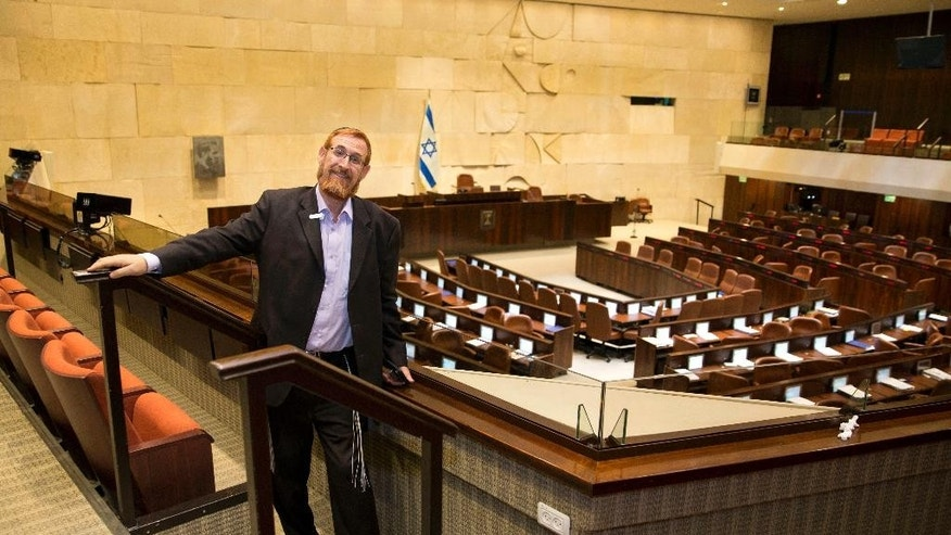 In this Thursday, June 2, 2016 photo, Knesset member Yehuda Glick, poses for a photo during an interview with The Associated Press at the Knesset, Israel's parliament, in Jerusalem. For years, Glick has pushed for greater Jewish access to Jerusalem's most sensitive holy site -- promoting an ideology that has unnerved Palestinians and made him the target of an assassination attempt. Now, as a new member of Israel's parliament, Glick is vowing to use his office to press his cause, bringing his explosive campaign to the nation's corridors of power. (AP Photo/Sebastian Scheiner)