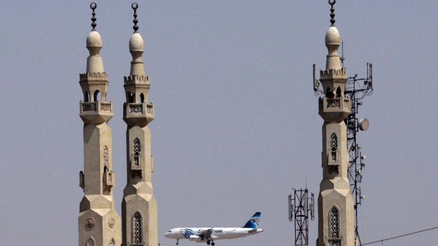 FILE - In this May 21, 2016 file photo, an EgyptAir plane flies past minarets of a mosque as it approaches Cairo International Airport, in Cairo, Egypt. Egyptians officials say a bomb threat has forced an EgyptAir airliner en route to Beijing from Cairo to make an emergency landing in Uzbekistan, where the aircraft is being searched. (AP Photo/Amr Nabil, File)