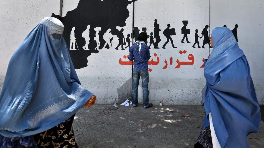 "In this Wednesday, May 25, 2016 photo, Women walk past an independent Afghan artist painting graffiti on a wall with Persian that reads, ""There is no peace in escaping,"" built to cordon off the Ministry of Communications in Kabul, Afghanistan. With every terrorist attack in Kabul, a little more of what made Afghanistan's capital a garden city of the 1960s disappears behind massive concrete walls designed to thwart suicide bombers and keep the people and buildings behind them safe. (AP Photo/Rahmat Gul)"