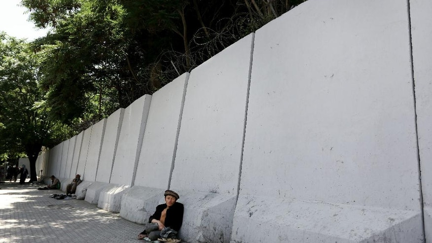 In this Wednesday, May 25, 2016 photo, an Afghan bigger sits in front of blast walls installed to cordon off the Ministry of Communications in Kabul, Afghanistan. With every terrorist attack in Kabul, a little more of what made Afghanistan's capital a garden city of the 1960s disappears behind massive concrete walls designed to thwart suicide bombers and keep the people and buildings behind them safe. (AP Photo/Rahmat Gul)